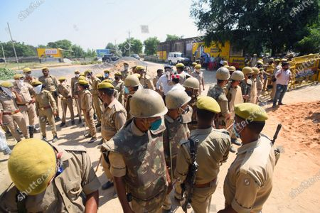 Uttar Pradesh Police personnel stand guard at the entrance to Hathras village, on October 2, 2020 in Hathras, India. A four-member delegation of the Trinamool Congress, led by senior party leader Derek O'Brien, was on Friday stopped by the police from going to the village of the 19-year-old gang-rape victim in Hathras of Uttar Pradesh to meet her family.