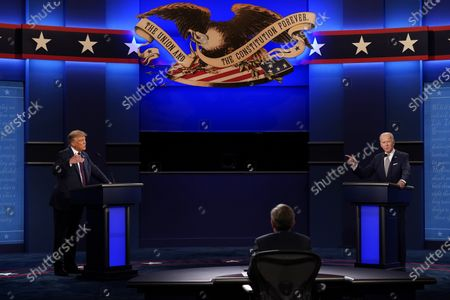 President Donald Trump, left, and Democratic presidential candidate former Vice President Joe Biden, right, with moderator Chris Wallace, center, of Fox News participate in the first presidential debate of the 2020 election at Case Western University and Cleveland Clinic, in Cleveland, Ohio. On Friday, Oct. 2, 2020, The Associated Press reported on stories circulating online incorrectly asserting that video footage and photos from the presidential debate show that Biden was wearing a wire. Biden's campaign confirmed to The Associated Press that the Democratic presidential candidate wore his late son Beau's rosary beads on his wrist last night at the debate. Another supposed wire location was a crease in his shirt