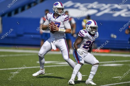 Buffalo Bills quarterback Josh Allen, left, looks to throw against the Los Angeles Rams as running back Devin Singletary blocks during the first half of an NFL football game, in Orchard Park, N.Y