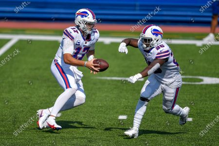 Buffalo Bills quarterback Josh Allen, left, fakes a hand off to running back Devin Singletary during the first half of an NFL football game against the Los Angeles Rams, in Orchard Park, N.Y