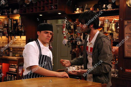 Jake Doland [James Baxter] Scratches a Scratch Card for Lizzie Lakely [Kitty Mcgeever] and Uncovers £500. Eli Dingle [Joseph Gilgun] Purposely Spills Lizzie's Pint and Grabs Jake and Tells Him to Keep His Mouth Shut.
