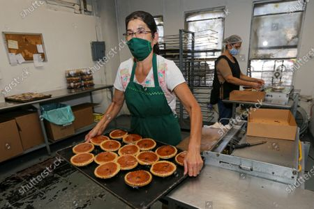 Maxi Rodriguez, left, and Guadalupe Palvodinos pack pies at 27th Street Bakery Shop on Tuesday, Sept. 29, 2020 in Los Angeles, CA. (Irfan Khan / Los Angeles Times)