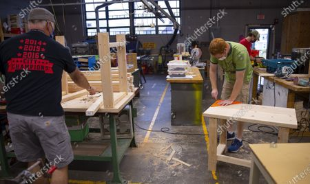 Nashua teachers John Lysik (L) Dan Scarpeti (R) and John Barry (C) assemble desks at the Elm Street School workshop in Nashua, New Hampshire, USA, 02 October 2020. Physical Education teacher John Barry started building the desks after seeing several of his students during online classes, working from kitchen tables, bedroom floors, and even a closet. He and fellow science teacher Dan Scarpeti, found an inexpensive desk plan and started making the desks, and other teachers soon joined in. As of this date, several thousand dollars have been pledged and the group plans to make desks for all students in need.