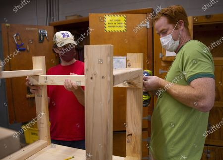 Physical Education teacher John Barry (R) and science teacher Dan Scarpeti (L) assemble a desk for a student in need at the Elm Street School workshop in Nashua, New Hampshire, USA, 02 October 2020. Physical Education teacher John Barry started building the desks after seeing several of his students during online classes, working from kitchen tables, bedroom floors, and even a closet. He and fellow science teacher Dan Scarpeti, found an inexpensive desk plan and started making the desks, and other teachers soon joined in. As of this date, several thousand dollars have been pledged and the group plans to make desks for all students in need.