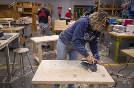 Eighth grade math teacher Cathy Belanger uses a sander on a newly built desk at the Elm Street School workshop in Nashua, New Hampshire, USA, 02 October 2020. Physical Education teacher John Barry started building the desks after seeing several of his students during online classes, working from kitchen tables, bedroom floors, and even a closet. He and fellow science teacher Dan Scarpeti, found an inexpensive desk plan and started making the desks, and other teachers soon joined in. As of this date, several thousand dollars have been pledged and the group plans to make desks for all students in need.