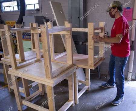 Science teacher Dan Scarpeti assembles a desk for a student in need at the Elm Street School workshop in Nashua, New Hampshire, USA, 02 October 2020. Physical Education teacher John Barry started building the desks after seeing several of his students during online classes, working from kitchen tables, bedroom floors, and even a closet. He and fellow science teacher Dan Scarpeti, found an inexpensive desk plan and started making the desks, and other teachers soon joined in. As of this date, several thousand dollars have been pledged and the group plans to make desks for all students in need.