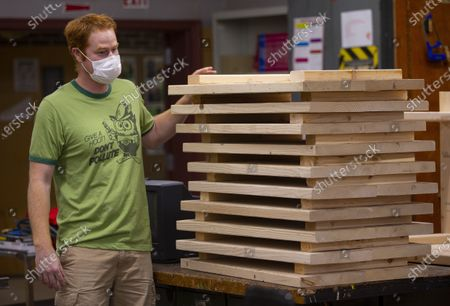 Physical Education teacher John Barry looks over a stack of desktops as he and other teachers volunteer to build and assemble desks for students in need at the Elm Street School workshop in Nashua, New Hampshire, USA, 02 October 2020. Physical Education teacher John Barry started building the desks after seeing several of his students during online classes, working from kitchen tables, bedroom floors, and even a closet. He and fellow science teacher Dan Scarpeti, found an inexpensive desk plan and started making the desks, and other teachers soon joined in. As of this date, several thousand dollars have been pledged and the group plans to make desks for all students in need.