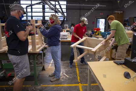 Nashua teachers John Lysik (L) Cathy Belanger (2L) Dan Scarpeti (2R) and John Barry (R) assemble desks for students in need at the Elm Street Middle School workshop in Nashua, New Hampshire, USA, 02 October 2020. Physical Education teacher John Barry started building the desks after seeing several of his students during online classes, working from kitchen tables, bedroom floors, and even a closet. He and fellow science teacher Dan Scarpeti, found an inexpensive desk plan and started making the desks, and other teachers soon joined in. As of this date, several thousand dollars have been pledged and the group plans to make desks for all students in need.