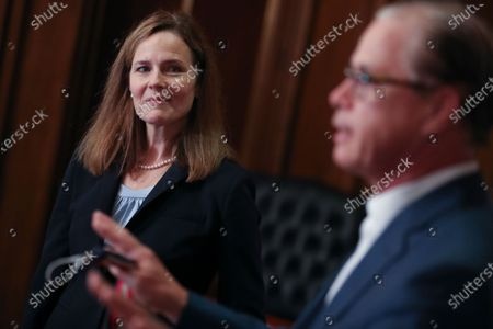 Amy Coney Barrett, U.S. President Donald Trump's nominee for associate justice of the U.S. Supreme Court, left, meets with Senator Mike Braun, a Republican from Indiana, at the U.S. Capitol in Washington, D.C., U.S.,. A bruising Senate confirmation fight over Trump's Supreme Court choice may seal the fates of several incumbent senators in the November election, though it has yet to drastically alter the odds for which party will control the chamber. Photographer: Oliver Contreras/Bloomberg (Photo by Oliver Contreras/Bloomberg)