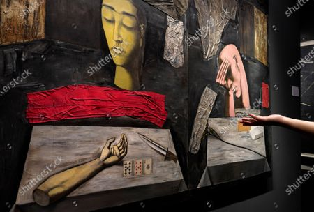 "Woman's hand is seen in front of a painting, ""The Dark Trilogy: Fear Meditation Sorrow"" by Chinese artist Zhang Xiaogang during the Sotheby's auction exhibition in Hong Kong . The work is estimated at US$3,230,000-5,810,000 and will be auction as part of the autumn sale"