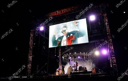 """Snoop Dogg is seen on a video monitor above the stage as he performs a DJ set as """"DJ Snoopadelic"""" during the """"Concerts In Your Car"""" series at the Ventura County Fairgrounds, in Ventura, Calif"""