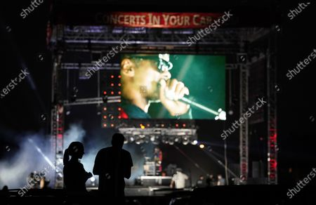 """Audience members are silhouetted as they watch Snoop Dogg perform as """"DJ Snoopadelic"""" during the """"Concerts In Your Car"""" series at the Ventura County Fairgrounds, in Ventura, Calif"""