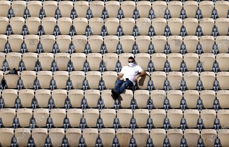 A spectator watches the third round match between Spanish players Roberto Bautista Agut and Pablo Carreno Busta on Court Suzanne-Lenglen at the French Open tennis tournament at Roland Garros in Paris, France, 03 October 2020.