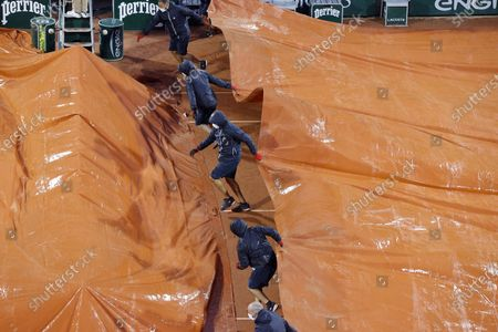 Staff covers the Court Suzanne Lenglen as rain interrupts the third round match of Garbine Muguruza of Spain against Danielle Collins of the USA during the French Open tennis tournament at Roland Garros in Paris, France, 03 October 2020.
