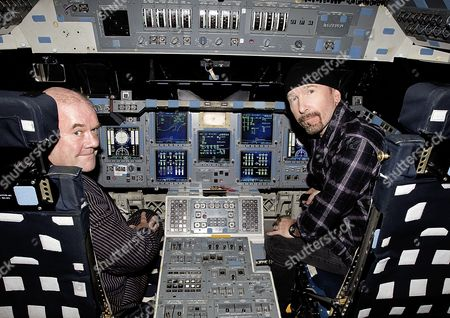 U2's manager Paul McGuinness and the Edge in the motion-based version of the Shuttle Mission Simulator at the Jake Garn Mission Simulation and Training Facility