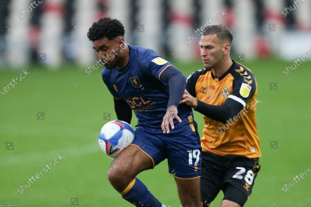 Jamie Reid of Mansfield Town controls under pressure from Mickey Demetriou of Newport County