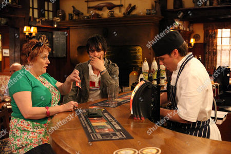 Stock Picture of Jake Doland [James Baxter] Scratches a Scratch Card for Lizzie Lakely [Kitty Mcgeever] and Uncovers £500. Eli Dingle [Joseph Gilgun] Purposely Spills Lizzie's Pint and Grabs Jake and Tells Him to Keep His Mouth Shut.