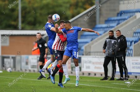 Tommy Smith of Colchester United and Cohen Bramall of Colchester United sandwich Sido Jombati of Oldham Athletic