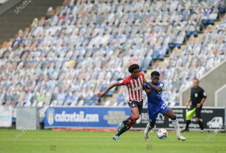 Kwame Poku of Colchester United and Sido Jombati of Oldham Athletic tussle for the ball