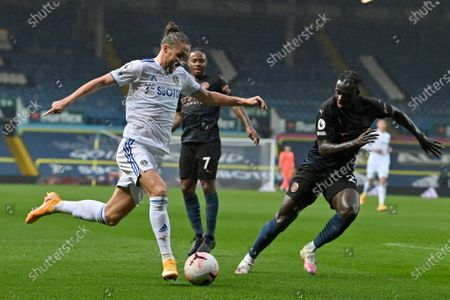 Leeds United's Luke Ayling, left, tries to get past Manchester City's Benjamin Mendy, right, during the English Premier League soccer match between Leeds United and Manchester City at Elland Road in Leeds, England