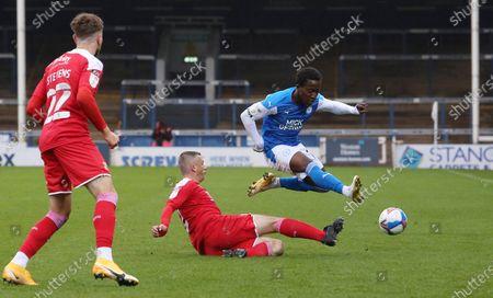 Siriki Dembele of Peterborough United skips over Paul Caddis of Swindon Town