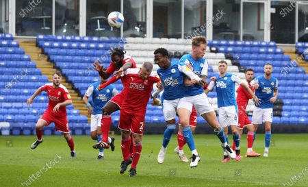 Siriki Dembele and Frankie Kent of Peterborough United challenge for the ball with Anthony Grant and Paul Caddis of Swindon Town