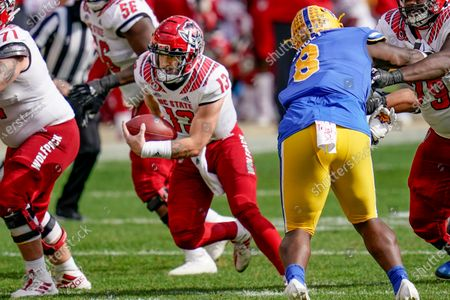 North Carolina State quarterback Devin Leary (13) scrambles for a first down past Pittsburgh defensive lineman Calijah Kancey (8) during the second half of an NCAA college football game, in Pittsburgh. North Carolina State won 30-29