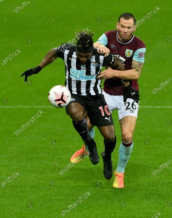 Newcastle's Allan Saint-Maximin, left, duels for the ball with Burnley's Phil Bardsley during the English Premier League soccer match between Newcastle United and Burnley at St. James' Park in Newcastle, England