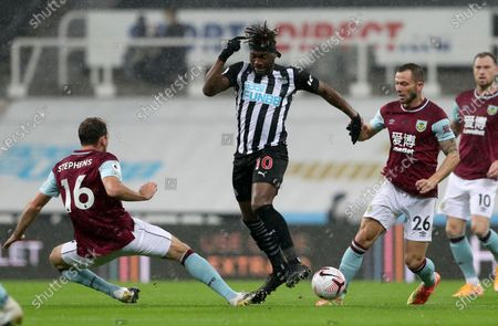 Newcastle's Allan Saint-Maximin, centre, duels for the ball with Burnley's Dale Stephens, left, and Burnley's Phil Bardsley during the English Premier League soccer match between Newcastle United and Burnley at St. James' Park in Newcastle, England