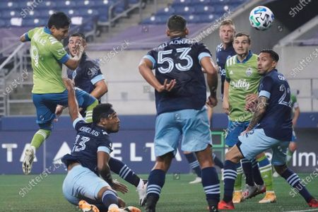 Seattle Sounders forward Raul Ruidiaz, left, watches his header against the Vancouver Whitecaps during the first half of an MLS soccer match, in Seattle