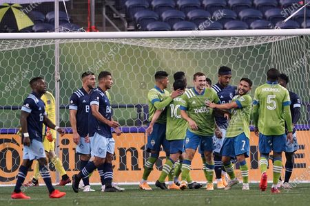 Seattle Sounders players celebrate after Raul Ruidiaz scored a goal against the Vancouver Whitecaps during the second half of an MLS soccer match, in Seattle