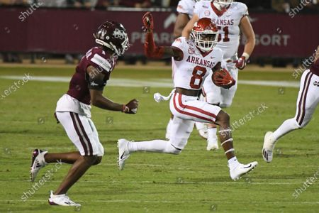 Arkansas wide receiver Mike Woods (8) looks for room past Mississippi State cornerback Martin Emerson (1) during the second half of an NCAA college football game in Starkville, Miss., . Arkansas won 21-14