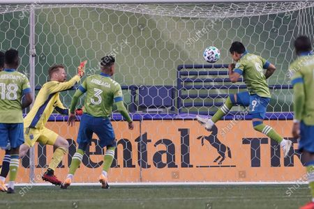 Stock Image of Seattle Sounders forward Raul Ruidiaz (9) scores a goal against Vancouver Whitecaps goalkeeper Bryan Meredith, second from left, during the second half of an MLS soccer match, in Seattle. The Sounders won 3-1