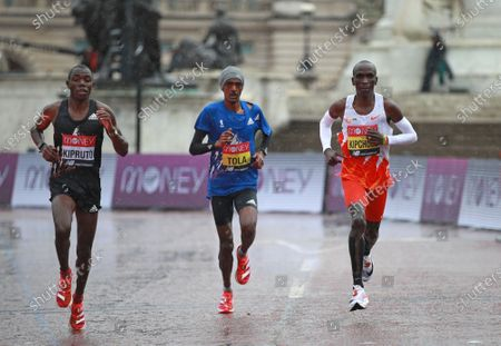 Kenya's Eliud Kipchoge, right, races to eight place during the London Marathon in London, England,. Athletes are competing on a 26.2-mile (42.2-kilometer) closed-loop course consisting of 19.6 clockwise laps around St. James' Park. The traditional course along the River Thames was scrapped because of the coronavirus pandemic and only elite men and women are competing and no spectators are permitted