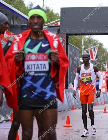 Kenya's Eliud Kipchoge, right, looks on after crossing the line in eighth place and behind Ethiopia's Shura Kitata, left, who won the London Marathon in London, England,. Athletes are competing on a 26.2-mile (42.2-kilometer) closed-loop course consisting of 19.6 clockwise laps around St. James' Park. The traditional course along the River Thames was scrapped because of the coronavirus pandemic and only elite men and women are competing and no spectators are permitted
