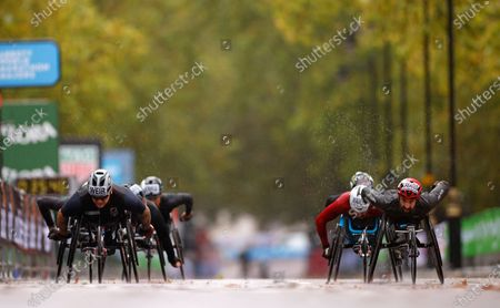 Britain's David Weir, left, and Canada's Brent Lakatos, right, compete in the men's elite wheelchair race at the London Marathon in London, England,. Athletes are competing on a 26.2-mile (42.2-kilometer) closed-loop course consisting of 19.6 clockwise laps around St. James' Park. The traditional course along the River Thames was scrapped because of the coronavirus pandemic and only elite men and women are competing and no spectators are permitted