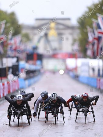 Switzerland's Marcel Hug, Britain's David Weir and Canada's Brent Lakatos, from left, race down the Mall during the London Marathon in London, England,. Athletes are competing on a 26.2-mile (42.2-kilometer) closed-loop course consisting of 19.6 clockwise laps around St. James' Park. The traditional course along the River Thames was scrapped because of the coronavirus pandemic and only elite men and women are competing and no spectators are permitted
