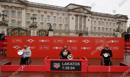 Stock Image of Canada's Brent Lakatos on the podium after winning the men's elite wheelchair race at the London Marathon in London, England, . At left is Britain's David Weir, second, and at right is Switzerland's Marcel Hug, third