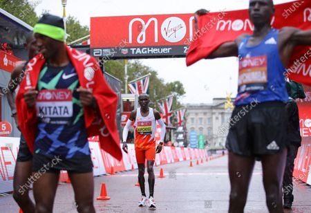 Kenya's Eliud Kipchoge, center, after crossing the line out of the places and behind Ethiopia's Shura Kitata, left, who won the London Marathon in London, England, . Athletes are competing on a 26.2-mile (42.2-kilometer) closed-loop course consisting of 19.6 clockwise laps around St. James' Park. The traditional course along the River Thames was scrapped because of the coronavirus pandemic and only elite men and women are competing and no spectators are permitted