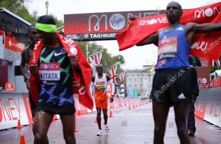 Eliud Kipchoge (C) of Kenya walks after he crossed a finish line of the elite men's race at the London Marathon in London, Britain, 04 October 2020.
