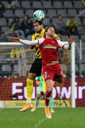 Emre Can (top) of Dortmund vies for header with Lucas Hoeler of Freiburg during a German Bundesliga match between Borussia Dortmund and SC Freiburg in Dortmund, Germany, Oct. 3, 2020.