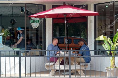 Patrons dine at a restaurant, in Winter Park, Fla. In his drive to return the state to normalcy, Republican Gov. Ron DeSantis lifted limits on indoor seating at restaurants, saying they can operate at 100% in municipalities with no restrictions and that other local governments can't restrict indoor seating by more than 50