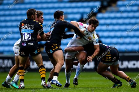 Tom Hendrickson of Exeter Chiefs is tackled by Jacob Umaga of Wasps and Tommy Taylor of Wasps