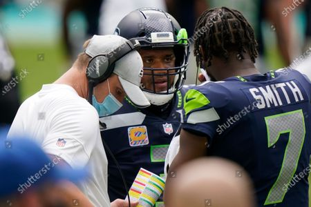 Seattle Seahawks quarterback Russell Wilson (3) listens to quarterback Geno Smith (7) on the sidelines, during the first half of an NFL football gam against the Miami Dolphins, in Miami Gardens, Fla