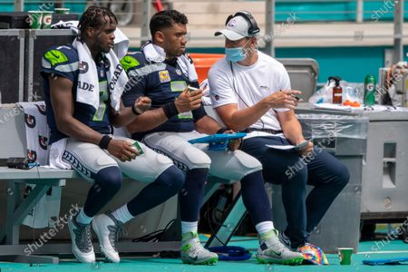 Seattle Seahawks quarterback Geno Smith (7), Seattle Seahawks quarterback Russell Wilson (3) speak with Seattle Seahawks quarterback coach Austin Davis as they sit on the bench on the sidelines as the Seahawks take on the Miami Dolphins during an NFL football game, in Miami Gardens, Fla