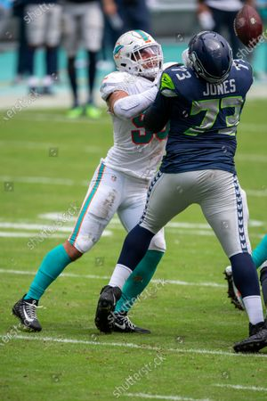 Seattle Seahawks tackle Jamarco Jones (73) strips the ball out of the hands of Miami Dolphins linebacker Kyle Van Noy (53) during an NFL football game, in Miami Gardens, Fla