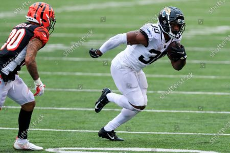 Stock Image of Cincinnati Bengals free safety Jessie Bates (30) defends as Jacksonville Jaguars running back James Robinson (30) carries the ball during an NFL football game in Cincinnati, . Cincinnati won 33-25