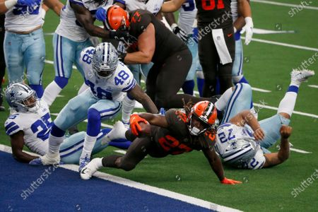 Cleveland Browns running back Kareem Hunt (27) reaches over the goal line to score a touchdown after getting through Dallas Cowboys' Xavier Woods (25), Joe Thomas (48), and Trysten Hill (72) in the first half of an NFL football game in Arlington, Texas
