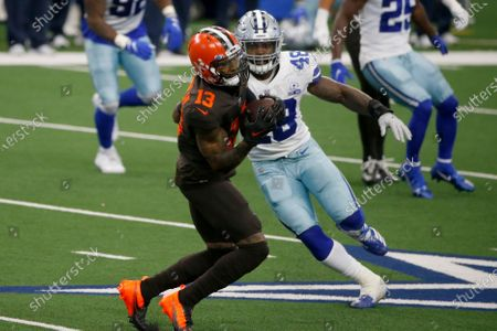 Cleveland Browns wide receiver Odell Beckham Jr. (13) catches a pass in front of Dallas Cowboys' Joe Thomas (48) in the first half of an NFL football game in Arlington, Texas