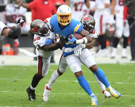 Los Angeles Chargers wide receiver Keenan Allen (13) is stopped by Tampa Bay Buccaneers inside linebacker Devin White (45) and cornerback Sean Murphy-Bunting (23) during the first half of an NFL football game, in Tampa, Fla